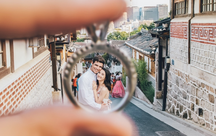 Engagement picture framed by a wedding ring,